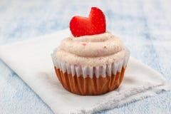 Jordgubbemuffin med jordgubbeglasyr på kaka och nya jordgubbehjärtor Arkivfoto