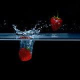 Jordgubben faller in i vatten Jordgubbar i luften Färgstänkwat Arkivfoto