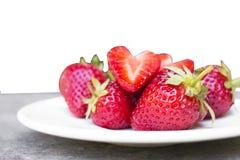 jordgubben i en maträtt som förlades på trät, isolerade vit bakgrund Royaltyfria Bilder