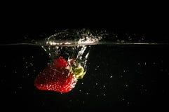 Jordgubben med en färgstänk avverkar in i vattnet, frukter i vattnet royaltyfri bild