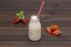 Jordgubbesmoothie eller milkshake i exponeringsglaskruset med sugrör med nya bär på träbakgrund arkivfoto