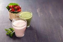Jordgubbesmoothies och en grönsakmilkshake i glass exponeringsglas står på en svart träbakgrund Royaltyfri Foto