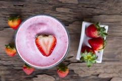 Jordgubbesmoothies och jordgubbefrukt för för milkshake på träsikt för bakgrund uppifrån arkivbilder