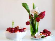 Jordgubbestilleben på på den vita plattan, med sund mat för orkidéblomma, sommar Berry Gardening fotografering för bildbyråer
