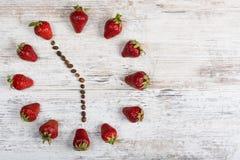 Jordgubbetid Jordgubbeklocka från kaffebönor som visar en tid av fem timmar femtiofem minuter eller sjutton timmar femtiofem Arkivbild