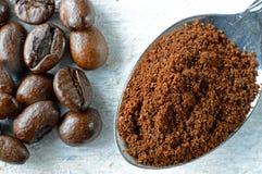 Jordkaffe i en sked och kaffebönor på en träbakgrund arkivbilder