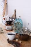 Jordkaffeblandning och nytt bryggat kaffe i en vit kopp med rottingsocker Träbufféräknare mycket av redskapet Arkivbilder