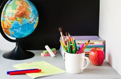 Jordklot, anteckningsbokbunt, blyertspennor och äpple på tabellen Skolbarn- och studentstudietillbeh?r tillbaka begreppsskola til fotografering för bildbyråer