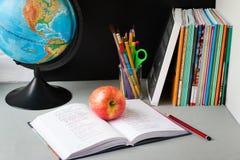 Jordklot, anteckningsbokbunt, blyertspennor och äpple på tabellen Skolbarn- och studentstudietillbeh?r tillbaka begreppsskola til arkivbilder