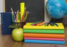Jordklot, anteckningsbokbunt och blyertspennor Skolbarn- och studentstudietillbehör Royaltyfri Bild
