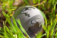 Jordklot för Crystal exponeringsglas i grönt gräs Royaltyfri Foto
