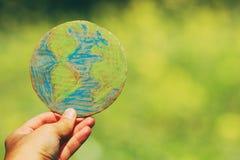 Jordklot för jord för manhandinnehav framme av utomhus- grön bokehbakgrund royaltyfri foto