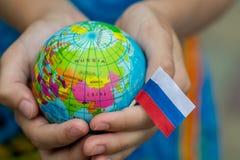 Jordklot i hand med den Ryssland flaggan, royaltyfri bild
