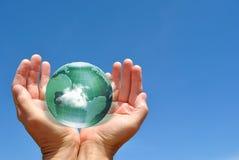 Jordklot i människahänder mot blå himmel Royaltyfri Fotografi