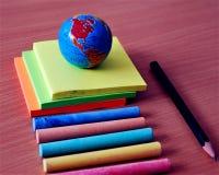Jordklot, klistermärkear, chalks och penna Arkivfoton