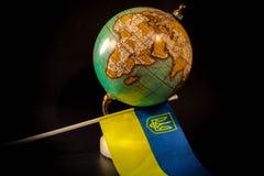 Jordklot med den ukrainska flaggan arkivfoton