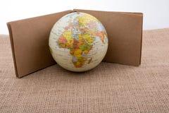 Jordklot med en anteckningsbok på kanfas arkivbilder
