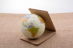 Jordklot med en anteckningsbok p? kanfas arkivbilder
