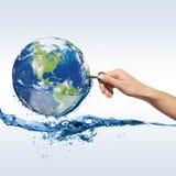 Jordklot med vatten och handen med tangenten Royaltyfri Fotografi