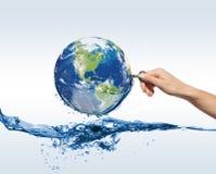 Jordklot med vatten och handen med tangenten Arkivbilder