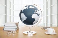 Jordklot och kaffe på skrivbordet Arkivbild