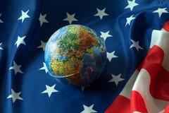 Jordklot som ligger på amerikanska flaggan Fotografering för Bildbyråer