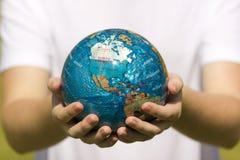 jordklotet hands barn Arkivfoto