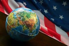 Jordklotet på bakgrunden av amerikanska flaggan Fotografering för Bildbyråer