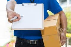Jordlott för innehav för leveransman och ge sigpenna till klienten royaltyfri bild