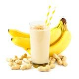 Jordnöt-smör banansmoothie med spridda ingredienser över vit Arkivbilder