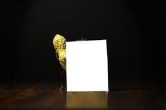 Jordnöt som rymmer ett tomt kort för annonsering Royaltyfri Foto