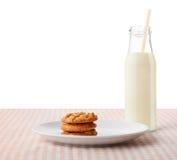 Jordnötsmörkakor på den vita plattan och flaskan av mjölkar Arkivfoton