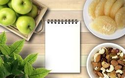 Jordnötter för äpplegrapefruktcoctail och vit anmärkningsbok under översikt Royaltyfri Fotografi