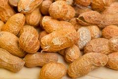 Jordnötter i shelles på trätabellen som en bakgrund Arkivfoto