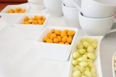 Jordnötter med guling och orange smet i vita behållare på Royaltyfri Foto