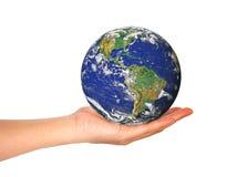 Jordplanet i den kvinnliga handen som isoleras på vit Fotografering för Bildbyråer