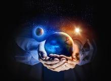 Jordplanet i händer Arkivfoto