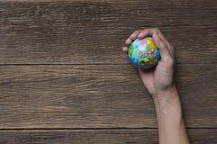 Jordplanet i kvinnlig hand på den wood tabellen Royaltyfri Foto