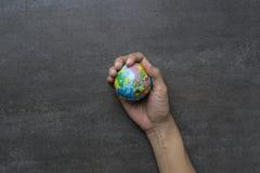 Jordplanet i kvinnlig hand på svart bakgrund Royaltyfria Foton