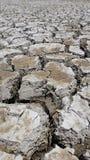 Jordtexturen av landtorkan som jordjordningen knäcker och ingen vattenbrist av fuktighet i torrt varmt väder Royaltyfria Bilder