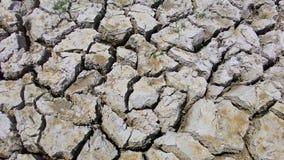 Jordtexturen av landtorkan som jordjordningen knäcker och ingen vattenbrist av fuktighet i torrt varmt väder Royaltyfri Foto