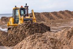 Jordvallar som fungerar sand för Dozermaskinskopa royaltyfri bild