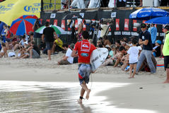 Jordy Smith - Quicksilver Pro. Jordy Smith running back to the competition area past spectators and media after catching a wave in his heat at the Quicksilver Royalty Free Stock Image