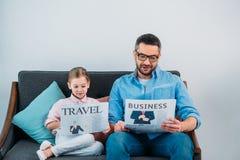 jornais da leitura do pai e da filha ao descansar no sofá fotos de stock royalty free