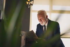 Jornais envelhecidos médios da leitura do homem de negócios imagens de stock royalty free