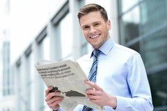 Jornal alegre da leitura do empresário foto de stock