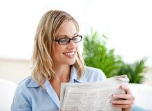 Jornal bonito da leitura da mulher de negócios com vidros Imagens de Stock Royalty Free