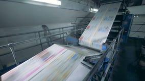 Jornal colorido que move sobre um transporte tipográfico, tecnologia moderna filme