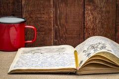 Jornal da expedição do vintage com um copo do metal do chá quente fotos de stock royalty free
