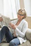 Jornal da leitura da mulher ao relaxar no sofá imagens de stock